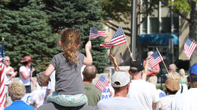 A criança acena a bandeira americana na reunião para fixar nossas beiras Fotografia de Stock Royalty Free