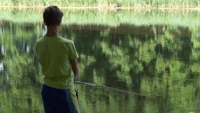 A criança adolescente trava uma vara de pesca na lagoa vídeos de arquivo