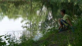 A criança adolescente trava uma vara de pesca na lagoa video estoque