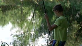 A criança adolescente trava uma vara de pesca na lagoa filme