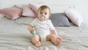 A criança adorável com olhos azuis bonitos está sentando-se na cama que suga no manequim video estoque