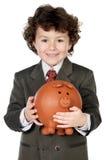 Criança adorável com suas economias em sua caixa de dinheiro de piggy Foto de Stock Royalty Free