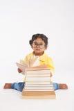 Criança adorável envolvida acima na leitura fotografia de stock