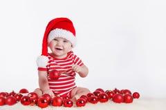 Criança adorável no tampão de Santa com as pilhas das caixas atuais em torno do assento no assoalho. Isolado no fundo branco Fotografia de Stock Royalty Free