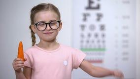 Criança adorável nos vidros que mostram os polegares até a cenoura, beta-carotina para os olhos vídeos de arquivo