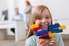 Criança adorável otimista que aprecia o jogo com grupo da construção Foto de Stock Royalty Free