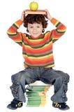Criança adorável que estuda com livros e maçã na cabeça Imagens de Stock