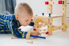 Criança adorável que joga com os brinquedos de madeira da construção Fotografia de Stock