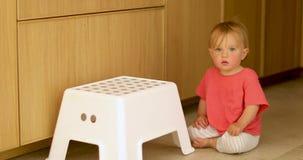 Criança adorável que senta-se no assoalho com cadeira branca vídeos de arquivo