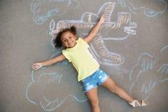 Criança afro-americano pequena que encontra-se perto do giz imagens de stock royalty free