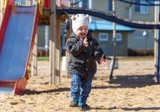 A criança agita fora suas mãos da areia no campo de jogos Imagem de Stock
