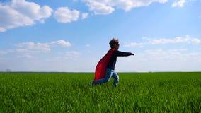A criança alegre em um traje do super-herói, em um casaco vermelho e em uma máscara corre através da grama verde, estica sua mão  video estoque