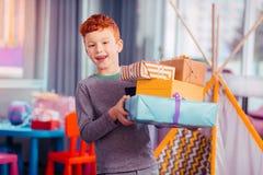 Criança alegre que demonstra suas caixas de presente coloridas imagens de stock