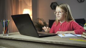 Criança alegre que faz trabalhos de casa em linha com portátil