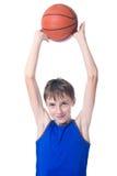 Criança alegre que guarda a bola para o basquetebol sobre sua cabeça Isolado no fundo branco Imagem de Stock Royalty Free