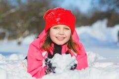 Criança alegre que joga na neve Menina feliz que tem o divertimento fora do dia de inverno Fotografia de Stock
