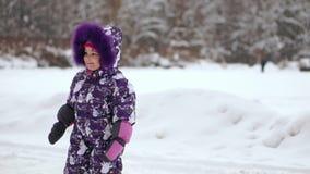 Criança alegre que joga na primeira neve no inverno Bebê dos anos de idade no terno morno da neve que anda e que tem o divertimen video estoque