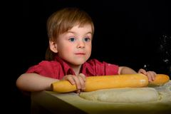 A criança amassa a farinha, a massa com rolos de um pino do rolo imagens de stock