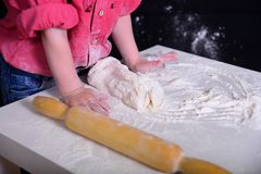 A criança amassa a farinha, a massa com rolos de um pino do rolo imagem de stock