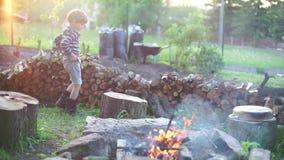 A criança anda em torno de um fogo video estoque