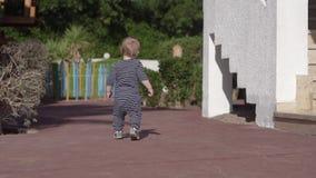 A criança anda na rua no movimento que lento listra dentro macacões vídeos de arquivo