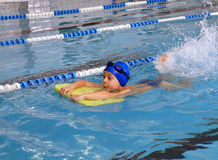 Criança 7 anos de menino que aprende nadar na associação de regaço. Foto de Stock Royalty Free
