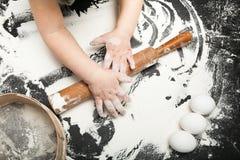 A criança aprende cozinhar em uma tabela preta, com farinha na cozinha imagem de stock royalty free