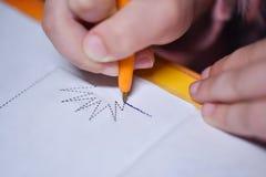 A criança aprende escrever e tira uma pena em torno da linha de contorno fotografia de stock royalty free
