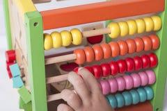 A criança aprende no conceito matemático usando grânulos de contagem coloridos Fotos de Stock