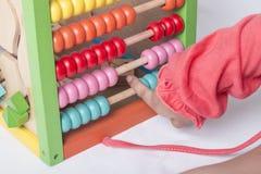 A criança aprende no conceito matemático usando grânulos de contagem coloridos Fotografia de Stock Royalty Free