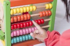 A criança aprende no conceito matemático usando grânulos de contagem coloridos Fotografia de Stock