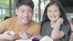 Criança asiática bonito que senta-se para apreciar o livro de leitura no café com cara do sorriso filme