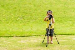 A criança asiática considerável toma uma foto pela câmera de DSLR Imagem de Stock