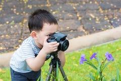A criança asiática considerável toma uma foto pela câmera de DSLR Fotografia de Stock Royalty Free