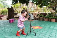 A criança asiática considerável toma uma foto pela câmera de DSLR Fotografia de Stock