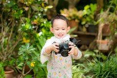 A criança asiática considerável toma uma foto pela câmera de DSLR Foto de Stock