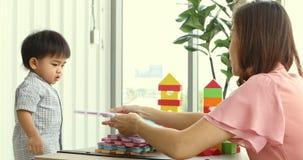 Criança asiática e sua mãe que jogam o enigma da espuma junto vídeos de arquivo