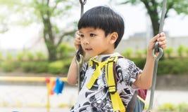 A criança asiática está balançando em um balanço Fotografia de Stock Royalty Free