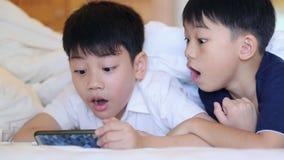 A criança asiática está jogando na tabuleta, sorrir, colocando na cama vídeos de arquivo