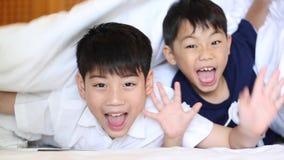A criança asiática está jogando o esconde-esconde na cama filme