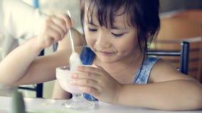A criança asiática feliz aprecia o gelado filme