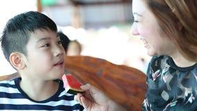A criança asiática feliz com mãe aprecia comer a melancia madura vídeos de arquivo