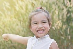 Criança asiática feliz da menina que levanta as mãos com felicidade fotos de stock