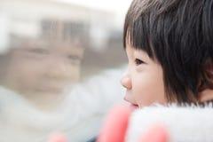 Criança asiática feliz que olha para fora a janela do trem fora Imagens de Stock Royalty Free