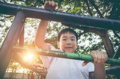 Criança asiática feliz que tem o divertimento no campo de jogos das crianças tonelada do vintage Fotografia de Stock Royalty Free