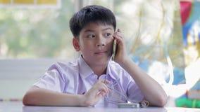 Criança asiática feliz que usa um telefone celular que chama com mamã video estoque