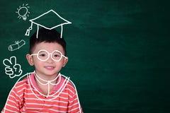 A criança asiática imagina seu dia graduado com o vestido graduado tirado mão no fundo, na educação e na graduação verdes do quad imagem de stock