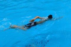 A criança asiática nada na piscina - estilo do rastejamento dianteiro Foto de Stock