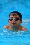 A criança asiática nada na piscina - o estilo da borboleta toma a respiração profunda Imagens de Stock