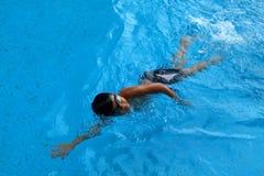 A criança asiática nada na piscina - o estilo do rastejamento dianteiro com poder scissor o pontapé Imagens de Stock Royalty Free